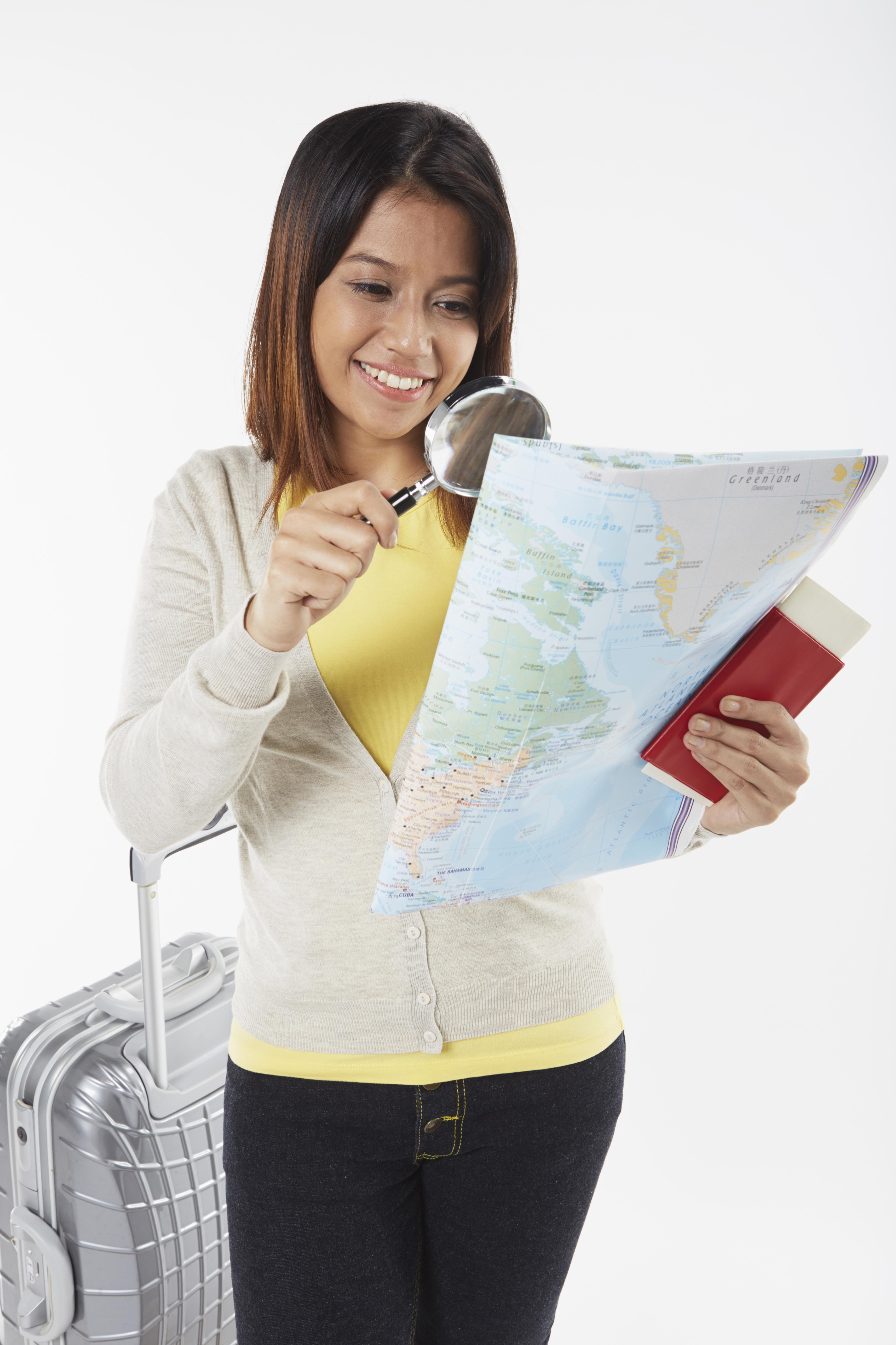 Woman-looking-at map-with-magnifying-glass